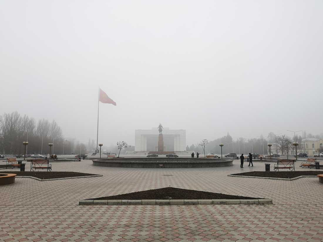 På det centrala torget Ala-Too vajar den kirgiziska flaggan i den tjocka smogen.