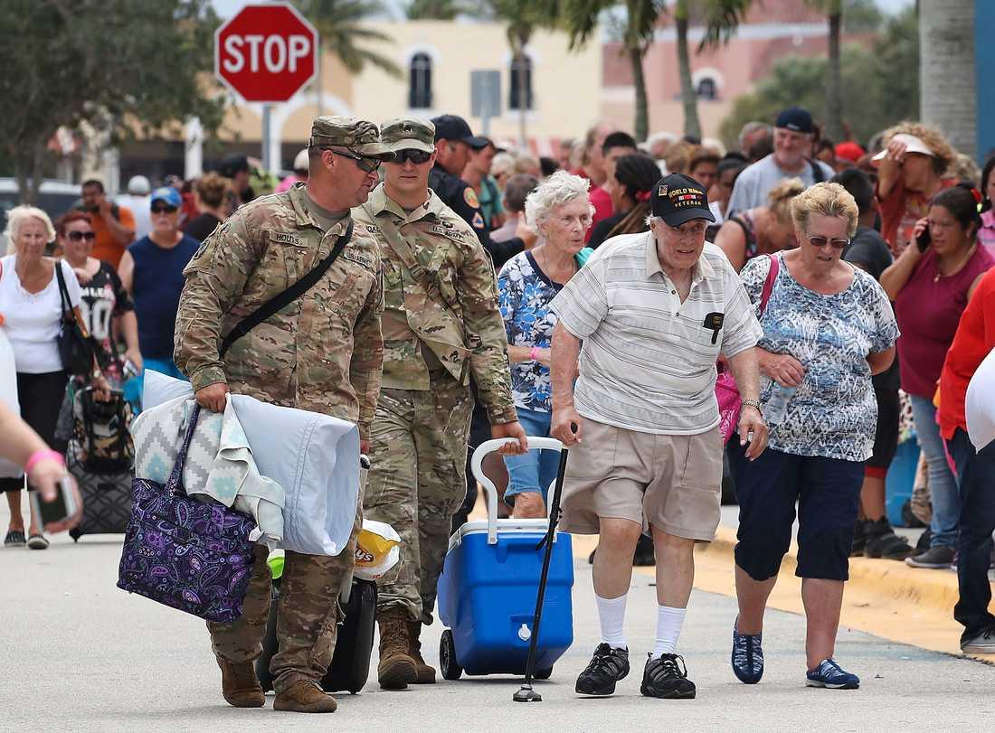 Anthony Gentuso, veteran från andra världskriget, får hjälp att bära tillhörigheter när han får skydd i Germain Arena i Estero, Florida.