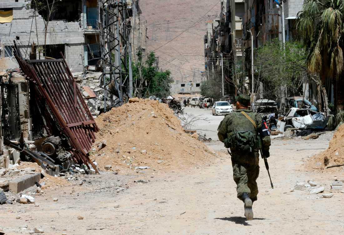 En rysk soldat springer i Douma utanför Damaskus.
