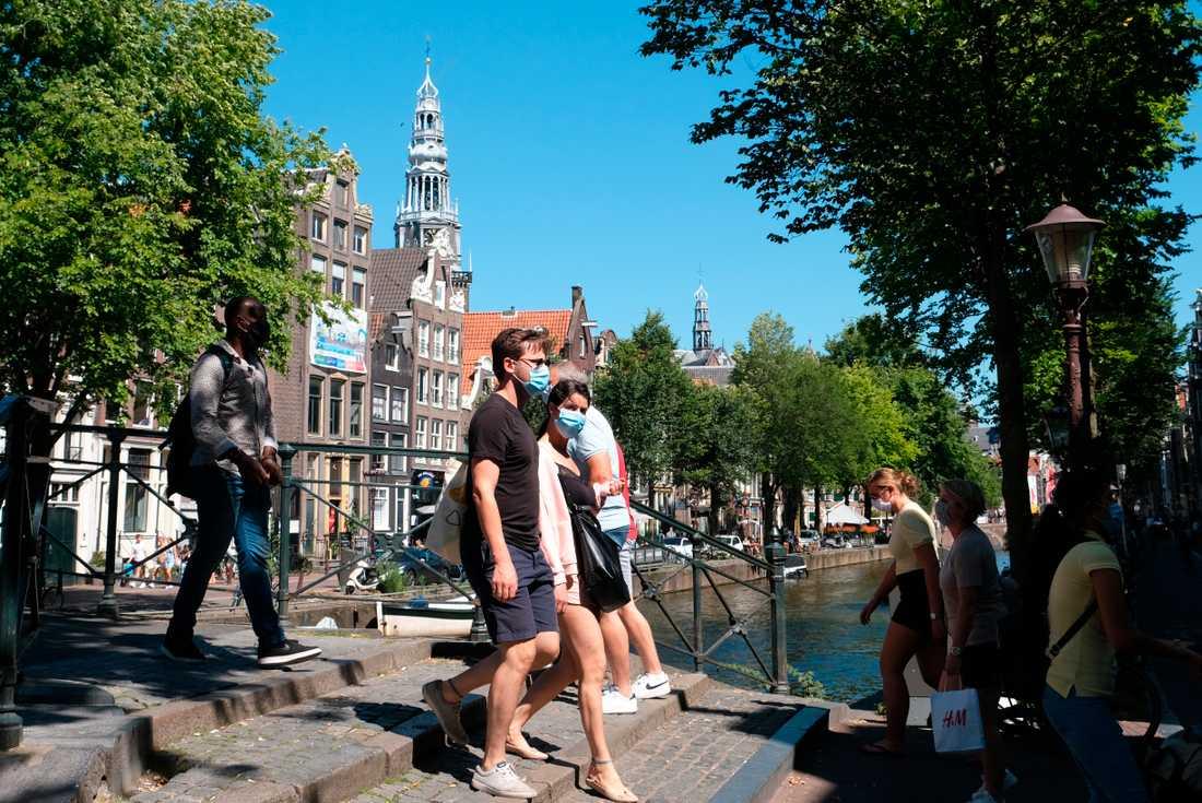 Människor promenerar över en bro i Nederländernas huvudstad Amsterdam, där krav på munskydd nyligen införts på vissa platser.