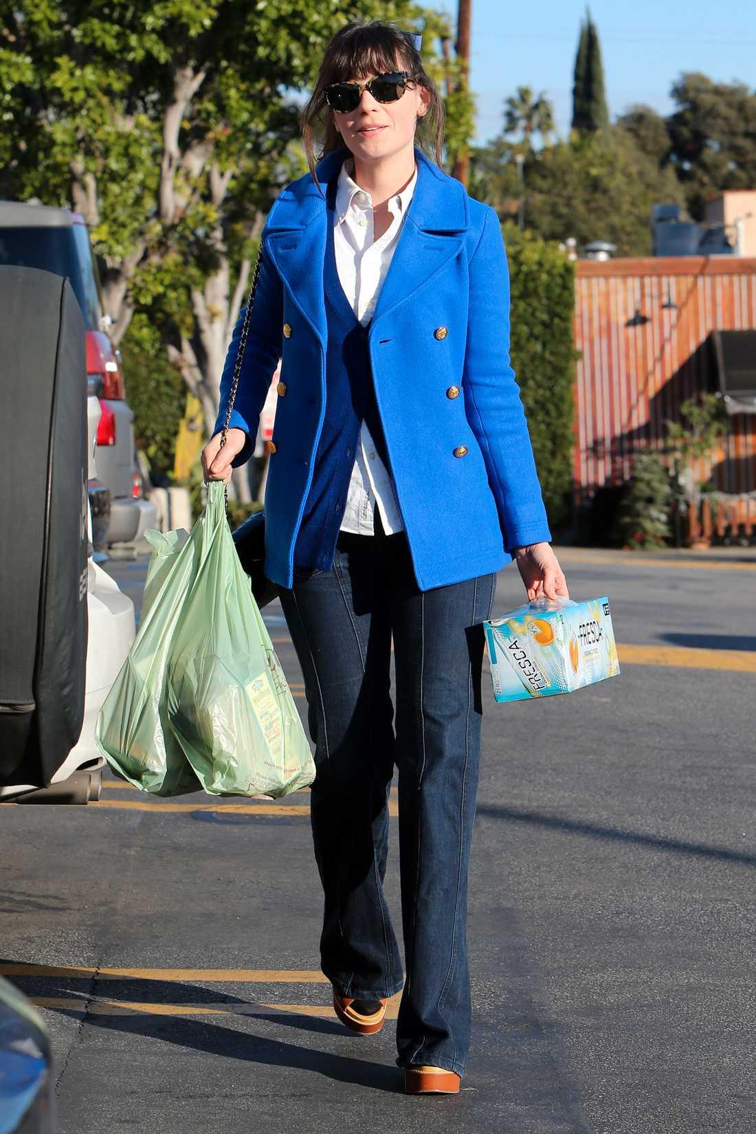 Söta Zooey Deschanel är 70-talsinspirerad i vida jeans, platåklackar och färggrann kort kappa.