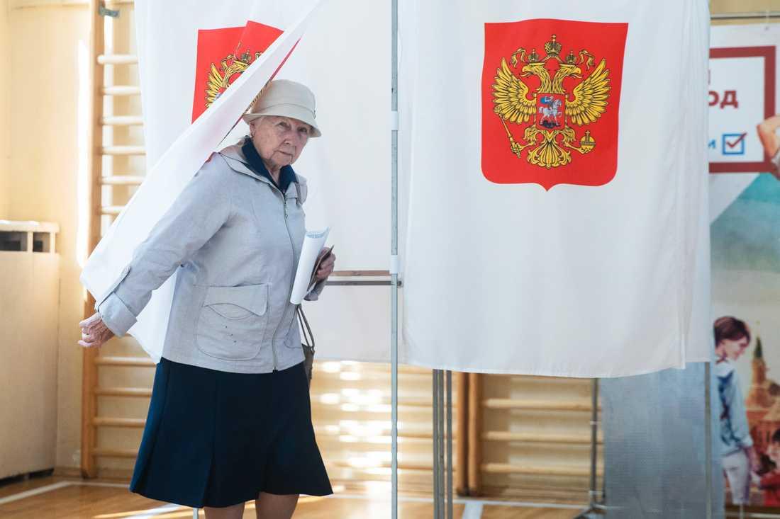 En kvinna lämnar röstbåset i en vallokal i Moskva vid söndagens val.