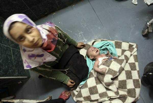 En palestinsk kvinna sitter på golvet bredvid sitt barn som skadades av en israelisk stridsvagn.