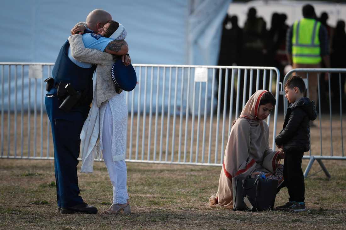 En polis kramar om en anhörig till ett av offren vid en begravningsplats i Christchurch.