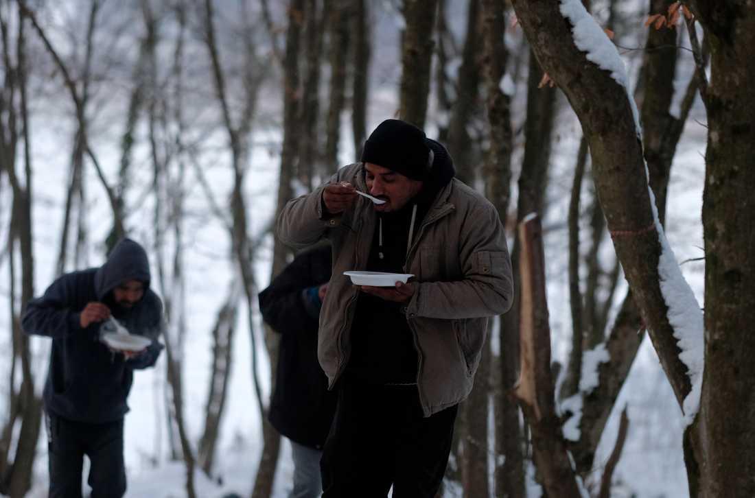 Migranter äter i ett tillfälligt läger utanför Velika Kladusa i Bosnien-Hercegovina, nära gränsen mot Kroatien. Arkivbild.