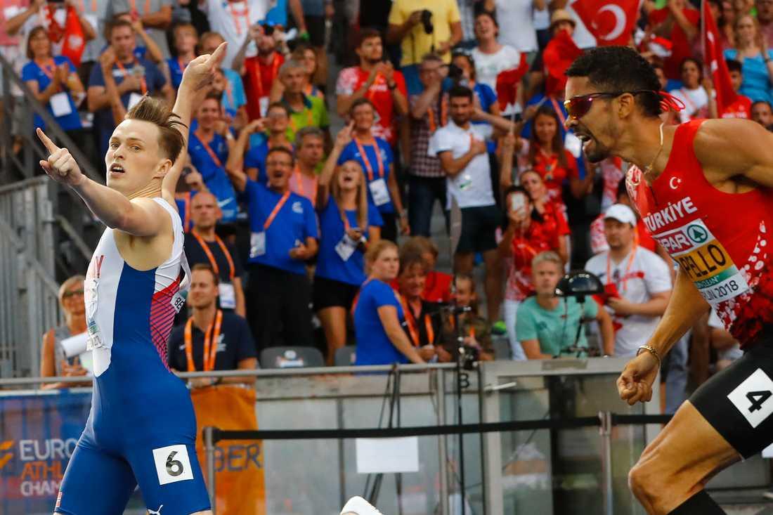Warholm gestikulerar för EM-guld vid målgången i gårdagens 400 meter häck-final. Hack i häl: turkiske Yasmani Copello som sedan försökte få norrmannen diskad.