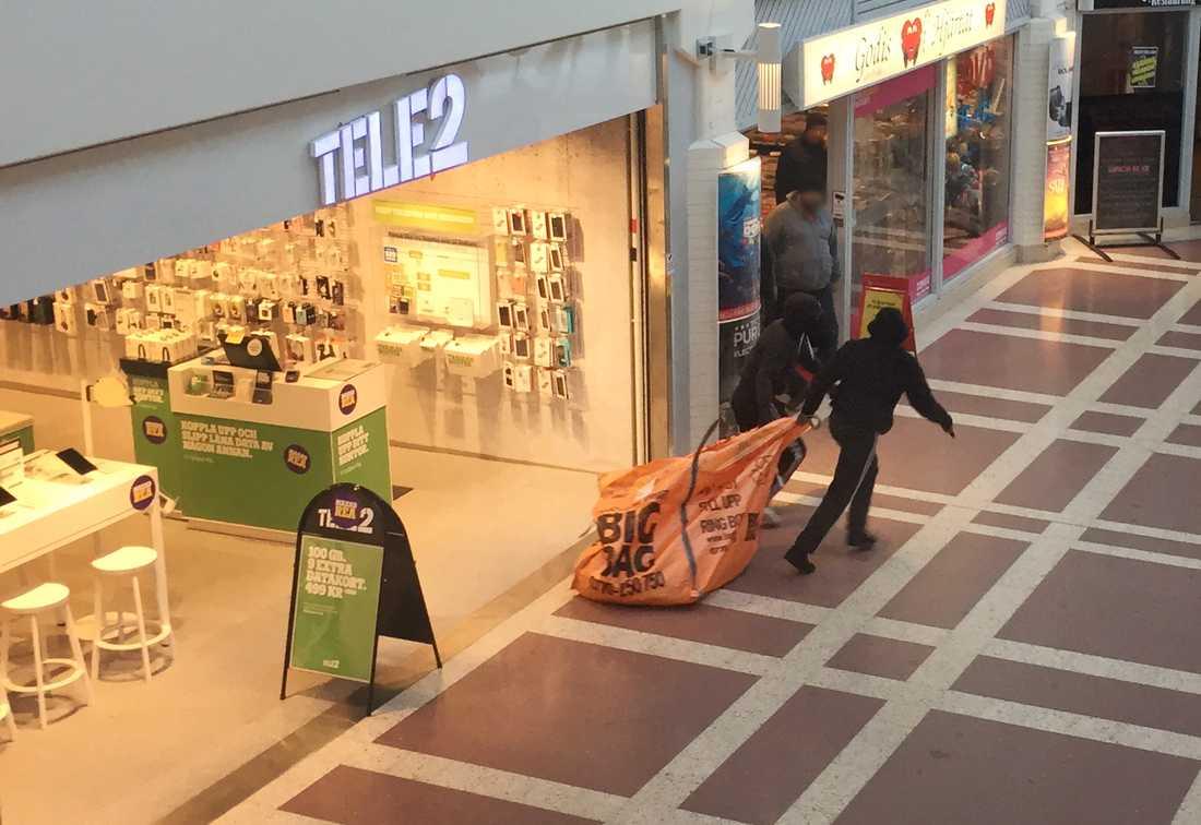 De två männen flydde från butiken med en stor väska, enligt de initiala uppgifterna var den fylld med mobiltelefoner och surfplattor.