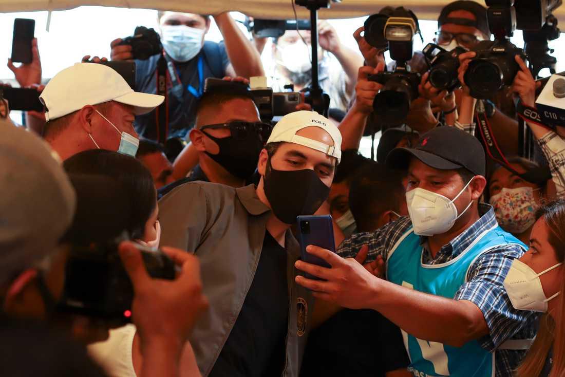 El Salvadors president Nayib Bukele, i vit keps, poserar för en selfie med en anhängare när han lägger sin röst i parlamentsvalet i söndags.