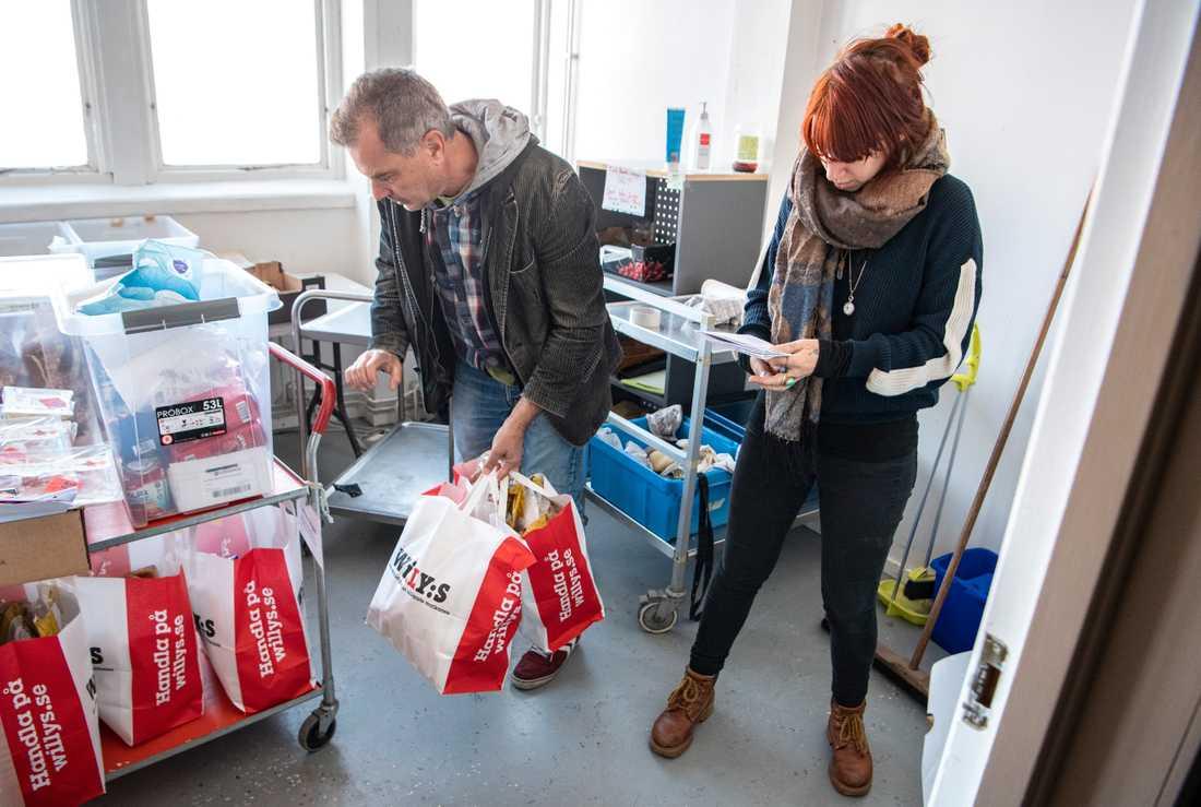 Volontär Johanna Anemalm tar emot en leverans med matsvinn som volontären Ulf Carlsson varit ute och hämtat i Malmö.