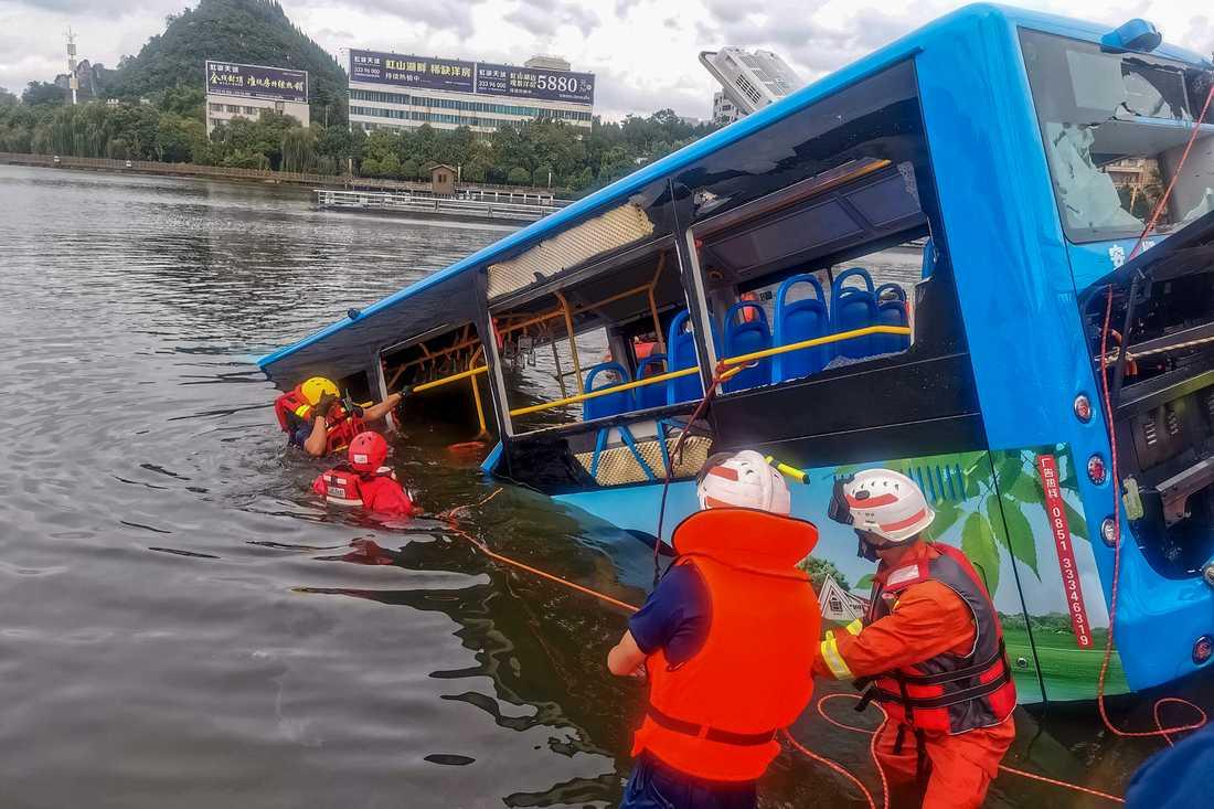 Räddningsarbetare bärgar bussen från sjön i kinesiska Anshun.