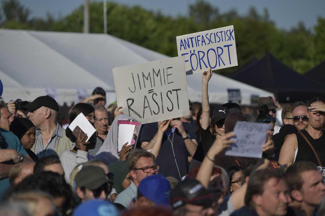 Folk i publiken höll upp plakat med ordet rasist.
