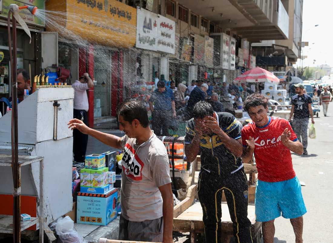 Heta somrar är vanliga i Irak. Här svalkar sig män på en gata i Bagdad i augusti 2016.