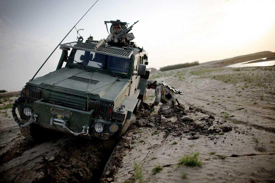 """En soldat försöker gräva loss fordonet som kallas """"Galten"""" från gyttjan."""