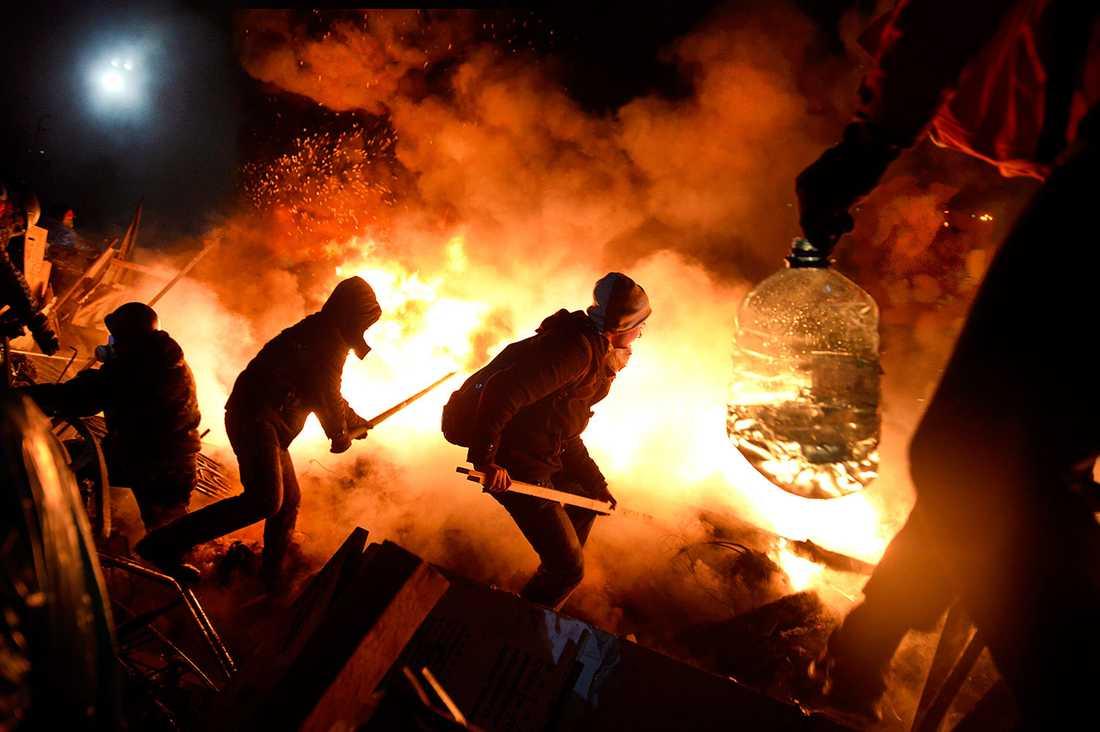 Demonstranter hjälps åt att att hålla liv i branden.