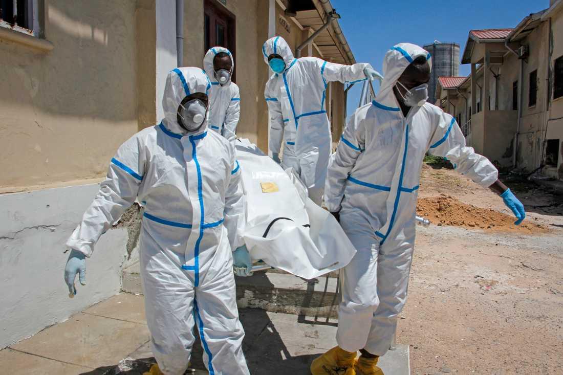 Vårdpersonal i skyddsutrustning hjälper till att transportera en kropp till en begravningsplats i Somalias huvudstad Mogadishu.