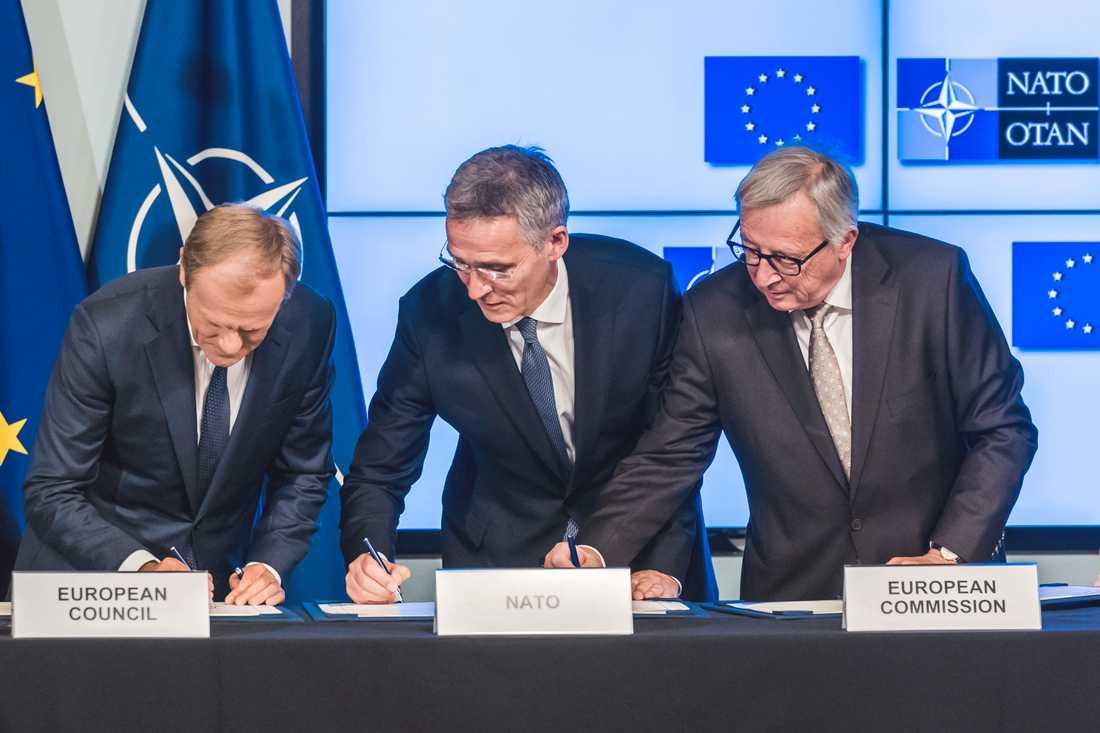 EU:s permanente rådsordförande Donald Tusk, Natos generalsekreterare Jens Stoltenberg och EU-kommissionens ordförande Jean-Claude Juncker skriver under ett samarbetsavtal.