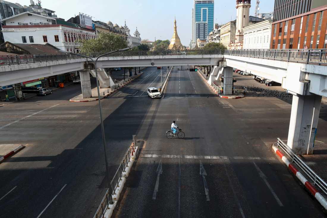 En cyklist på en glest trafikerad gata i staden Rangoon i Myanmar. Arkivbild.