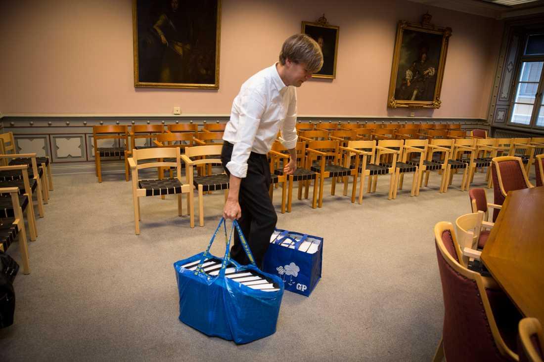 Pelle Almqvist bär in kassar med material till förhandlingarna.