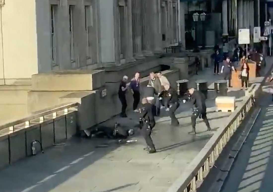 Polisen omringar en misstänkt gärningsman efter knivattacken vid London Bridge. Bilden är en skärmdump från ett videoklipp.