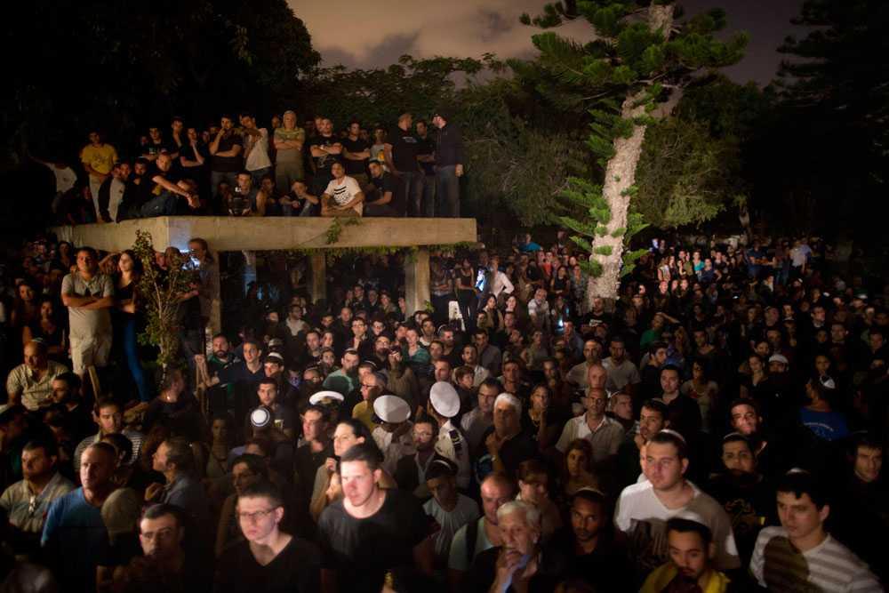 Tusentals israeler deltar under begravningen av den israeliske soldaten Nissim Sean Carmeli. Han är en av 13 israeliska soldater som dör den 20 juli.