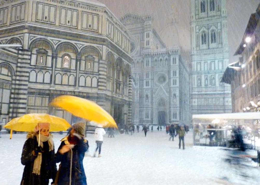 Insnöade Människor skyddar sig med paraplyer i nedsnöade Florens, Italien.