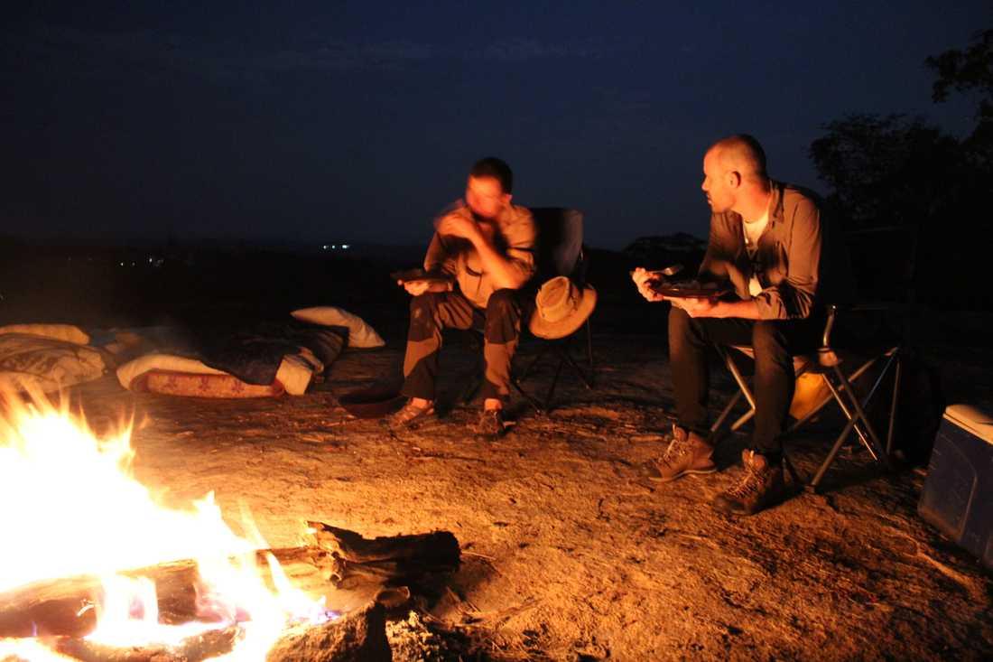 Martin Stenmarck diskuterar tjuvjakt med parkvakter i Zimbabwe runt lägerelden.