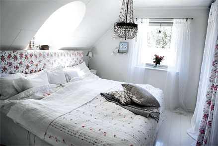 Det ljusa sovrummet andas romantik med sin blandning av blommor och kristallkronan i taket.