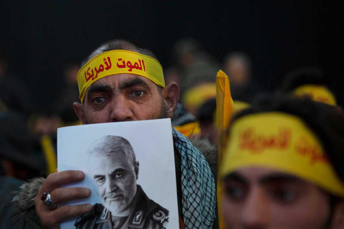 En anhängare till Iranstödda Hizbollah i Libanon håller upp en bild som föreställer den dödade generalen Qassem Soleimani.