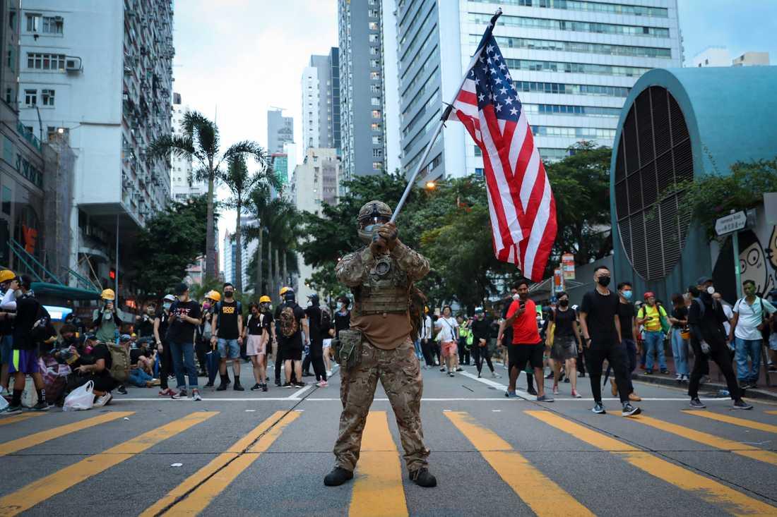 En demonstrant utklädd till militär håller en amerikansk flagga under demokratiprotester i Hongkong i augusti 2019.
