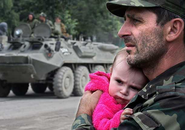 En sydossetisk militär håller ett barn i sin famn medan han tittar på militärfordonen, i staden Dzhava.