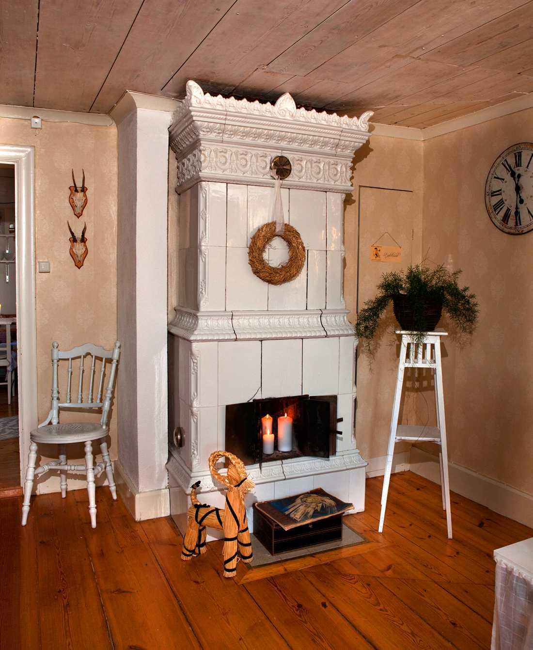 MYSFAKTOR. Det går visserligen inte att elda i kakelugnen i vardagsrummet, men med tjocka tända ljus i eldstaden sprider den ändå en varm atmosfär.