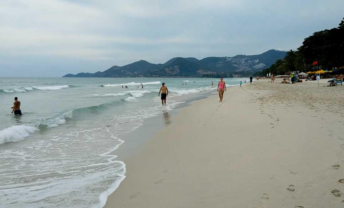 En strand på thailändska Koh Samui. I bakgrunden syns en röd flagga, som varnar för det kommande stormvädret.