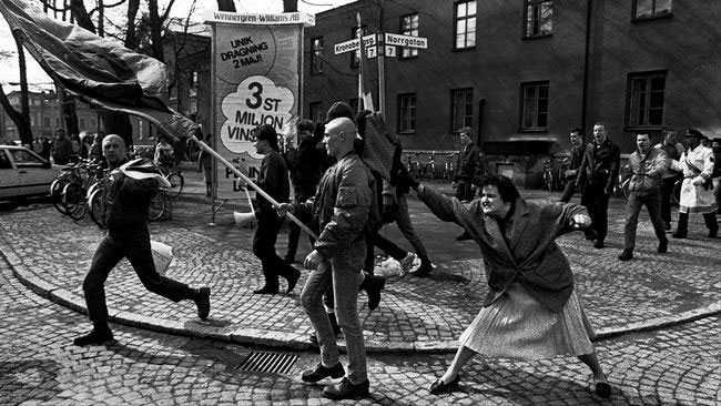"""Flera jämför bilden med det klassiska fotot som brukar kallas """"tanten med väskan"""" som visar en kvinna i Växjö 1985 som attackerar en demonstrant från Nordiska rikspartiet med en väska."""