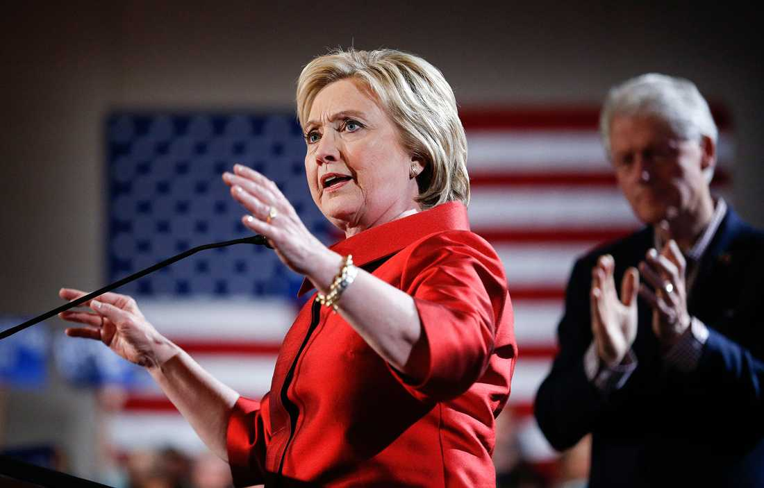 Hillary Clinton med maken Bill i bakgrunden.