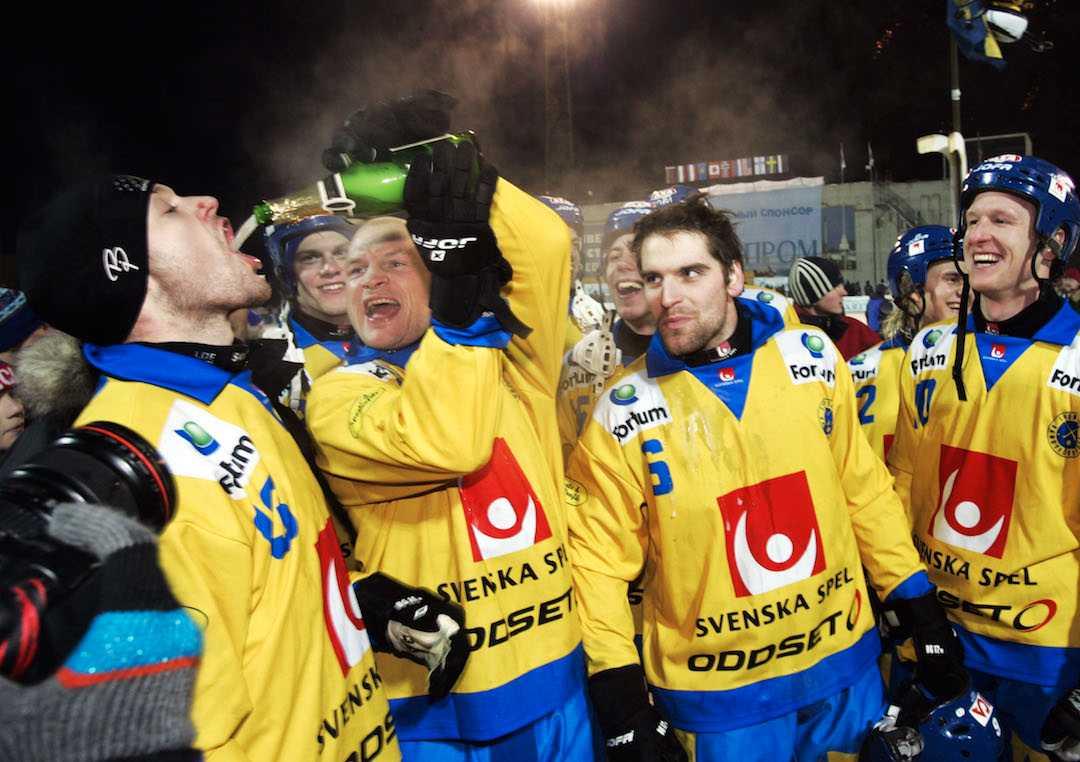 """Fosshaug serverar Anders Östling skumpa efter VM-titeln 2005. Andreas Westh och Stefan """"X:et"""" Erixon tittar på."""