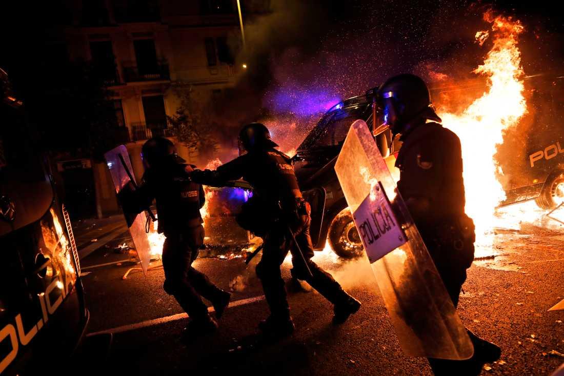 Poliser springer undan när en polisbuss fattar eld vid protesterna i Barcelona.