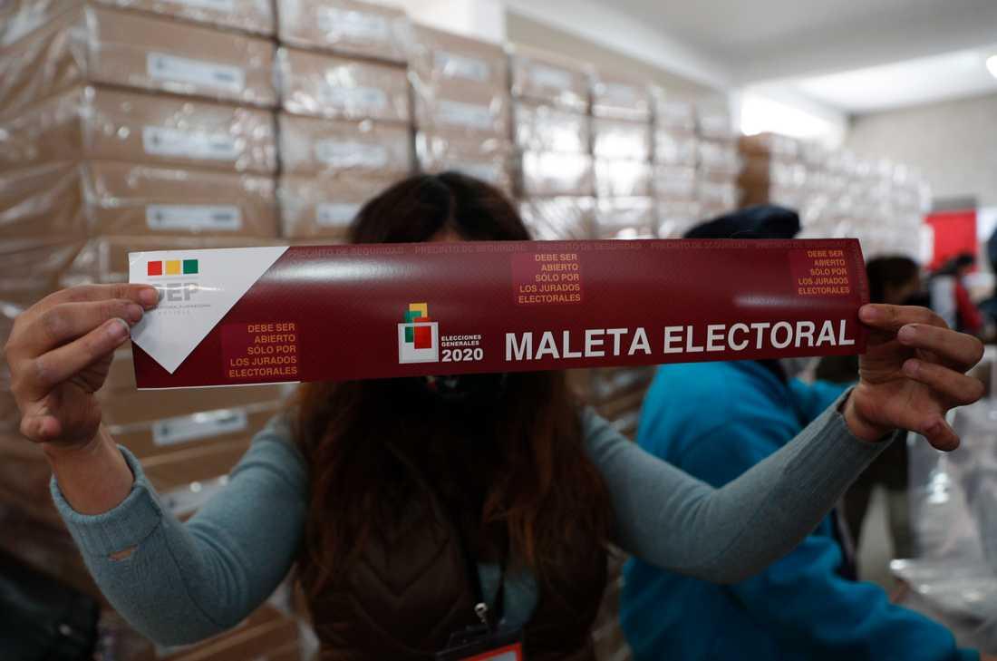 En valarbetare visar upp röstmaterial i La Paz inför valdagen.