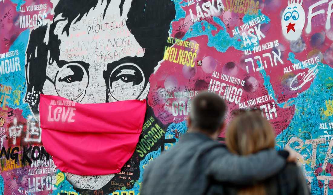 """I dag minns många John Lennon, som blev skjuten till döds i New York för 40 år sedan. Här betraktar ett par """"Lennon-väggen"""" i Prag, där hans porträtt fått ett munskydd under pandemin."""