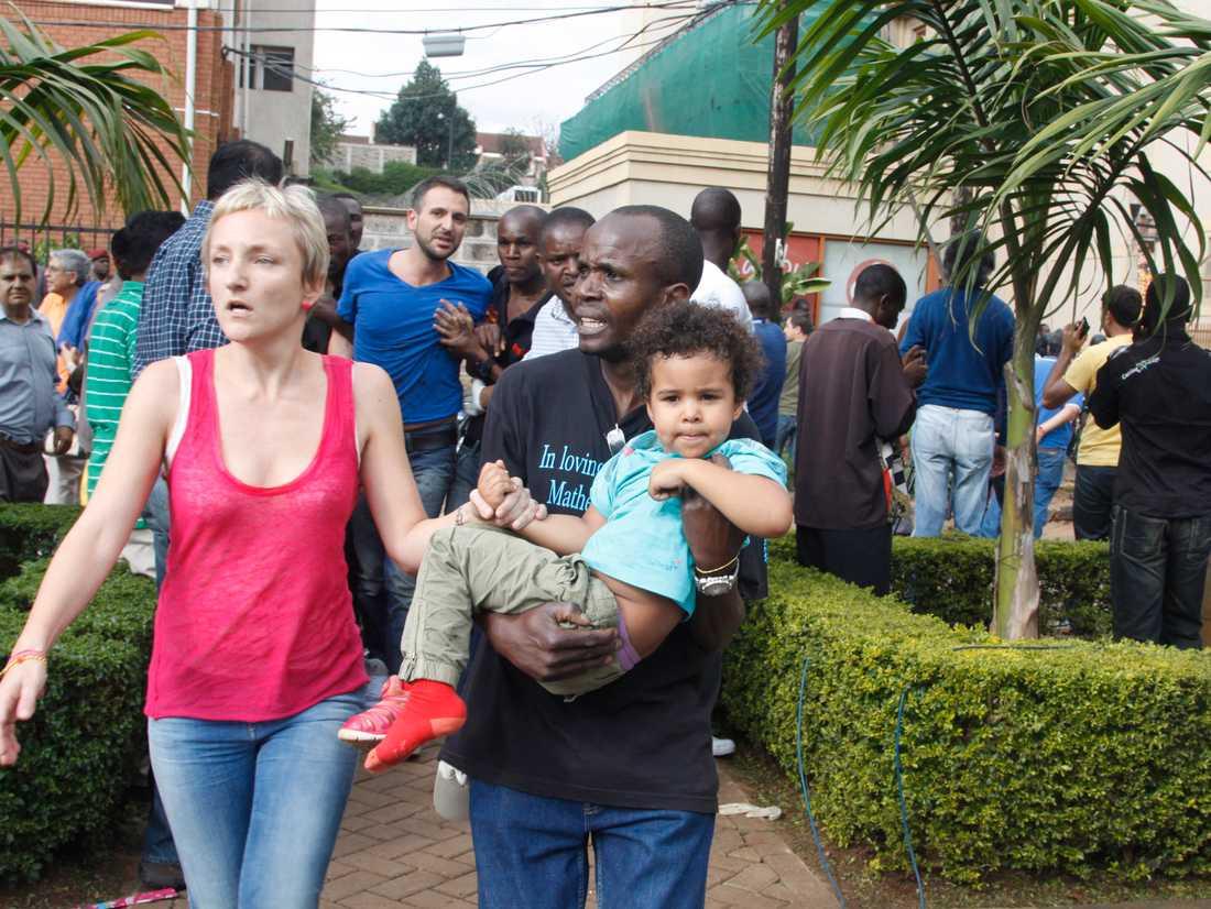 En mamma och en säkerhetsvakt tar hand om ett barn utanför shoppingcentret.