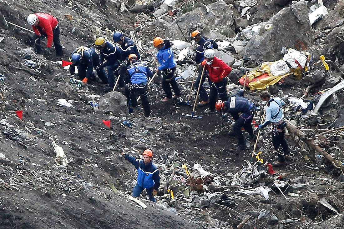 Räddningspersonal finkammar platsen där planet kraschade.