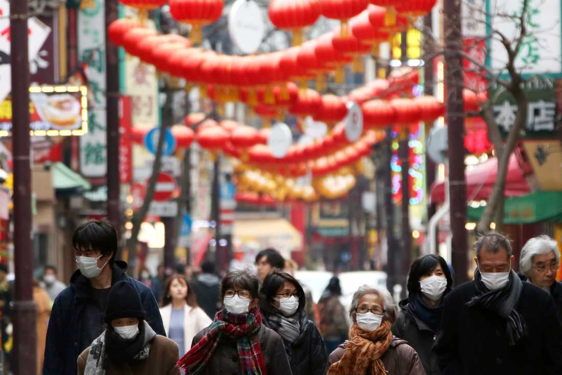 Människor i ansiktsmundering i Chinatown-området i Yokohama, Japan.