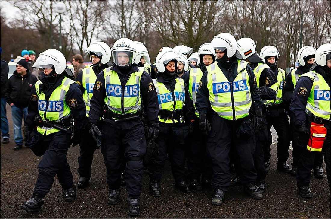 Poliser stoppar demonstranterna.