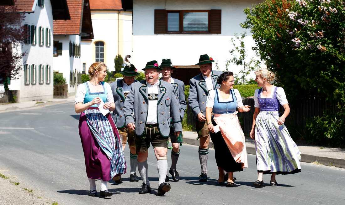 Traditionellt klädda invånare i Haunshofen i Tyskland på väg mot vallokalen.