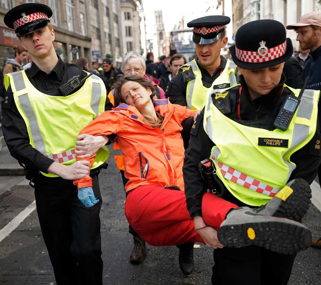 En demonstrant bärs bort sedan hon blockerat trafiken utanför Goldman Sachs i London den 25 april i år.