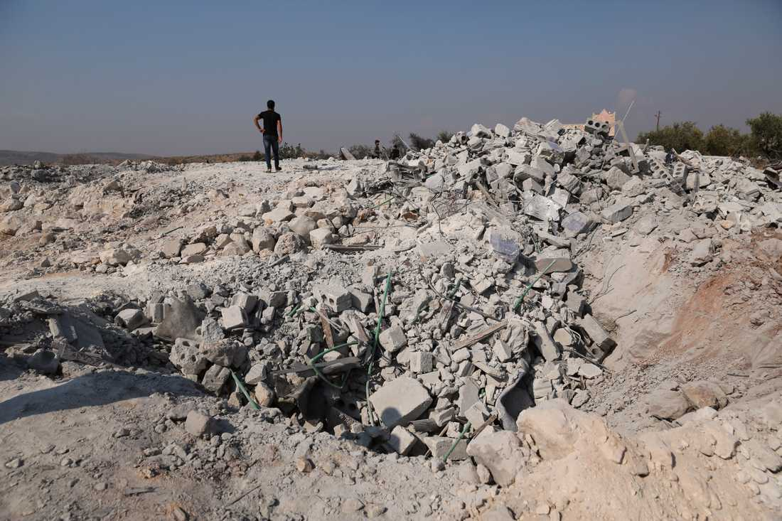 Personer går runt bland resterna av det hus där USA säger att IS-ledaren Abu Bakr al-Baghdadi dödades.