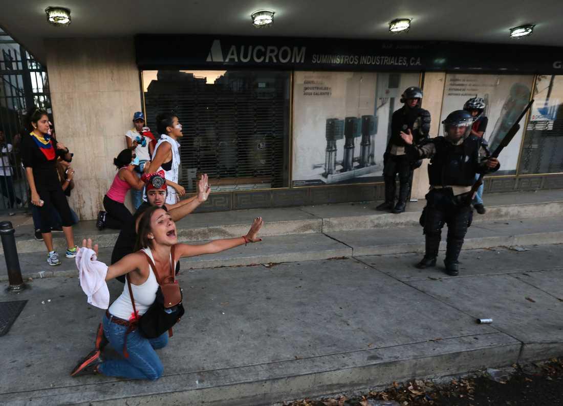 En demonstrant från oppositionen vädjar till polisen att inte skjuta tårgas.