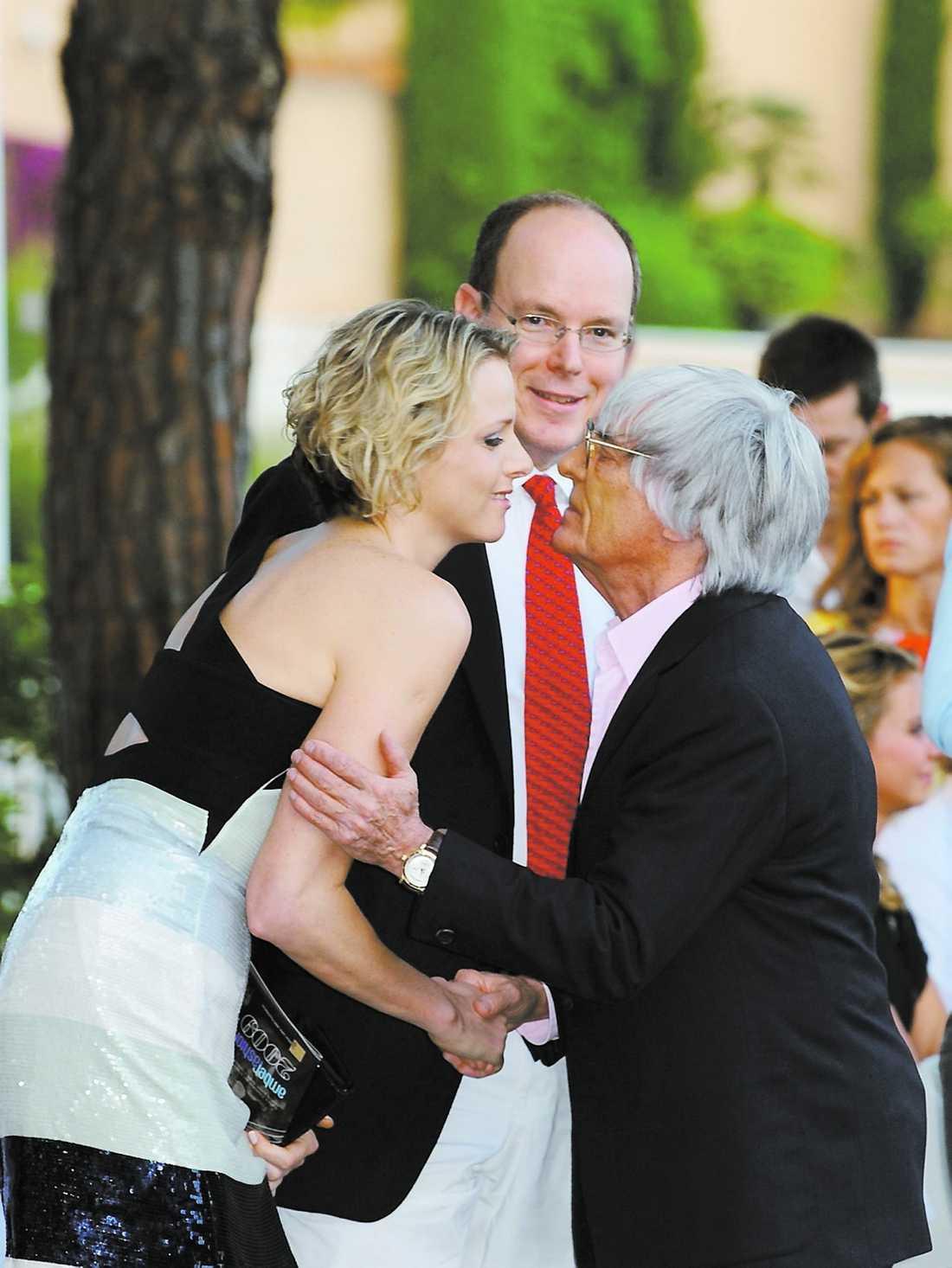 Prince Albert II av Monaco och flickvännen Charlene Wittstock hälsar på Bernie Ecclestone under luxuösa Amber Fashion Show.