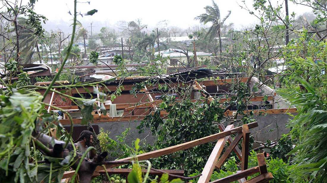En man i huvudstaden Port Vila vid ett demolerat hus.