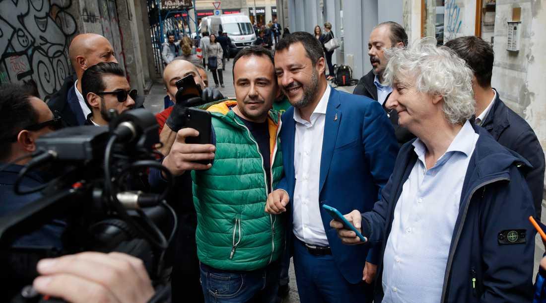 Italiens inrikesminister och vice premiärminister Matteo Salvini i blå kavaj ställer upp på selfies i samband med att han ska hålla en presskonferens i Milano.