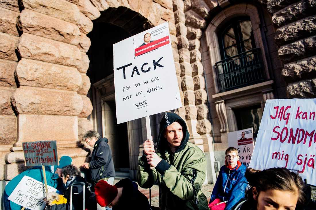 """""""Tack för att ni gör mitt liv ännu värre"""", står det på det plakat som Justus Bengtsson-Korsås, 15, höll upp vid den demonstration mot nedskärningarna i assistansen som han hade arrangerat utanför Riksdagshuset under fredagen."""